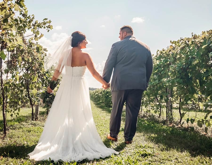 Groom and bride walking in the vineyard at Pedretti's Party Barn in Viroqua, Wisconsin